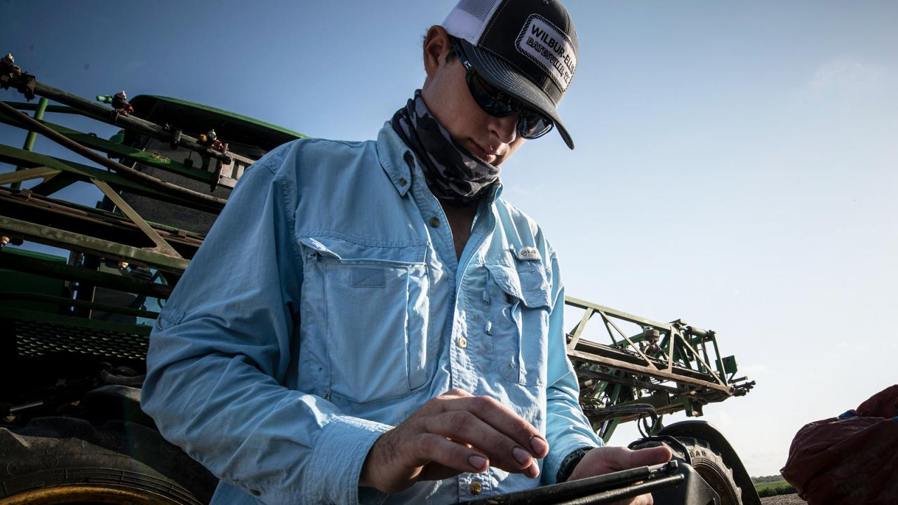 Man on tablet in front of sprayer machine.