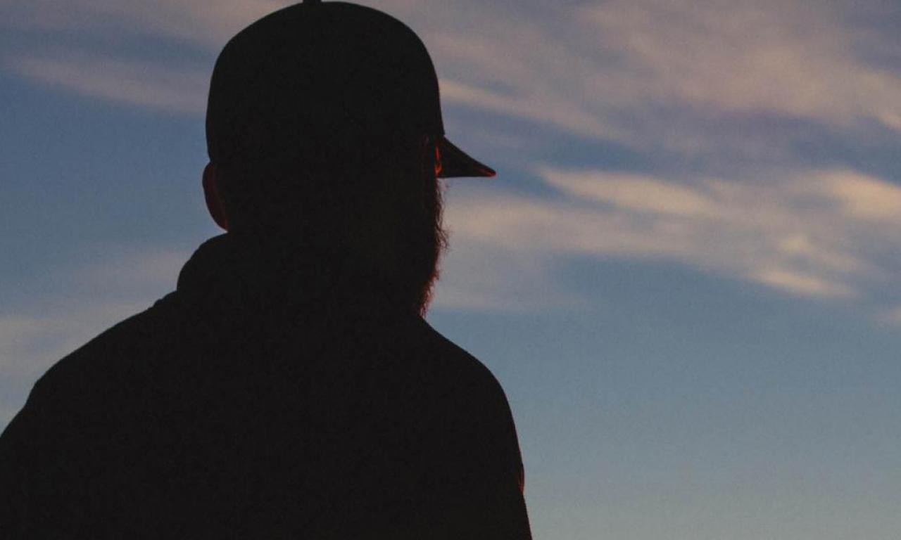 Silhouette of man looking over horizon.