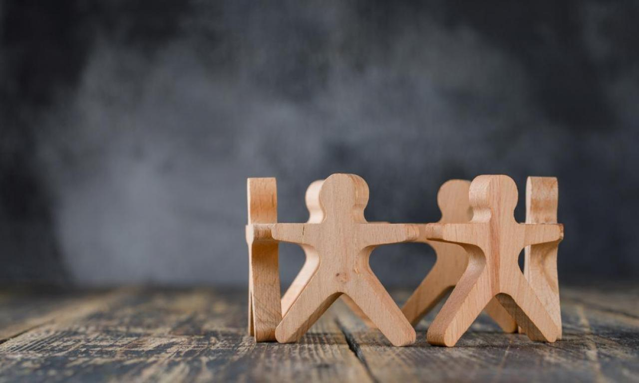 Wooden figures of people holding hands on table.