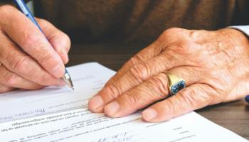 Hand signing a document.